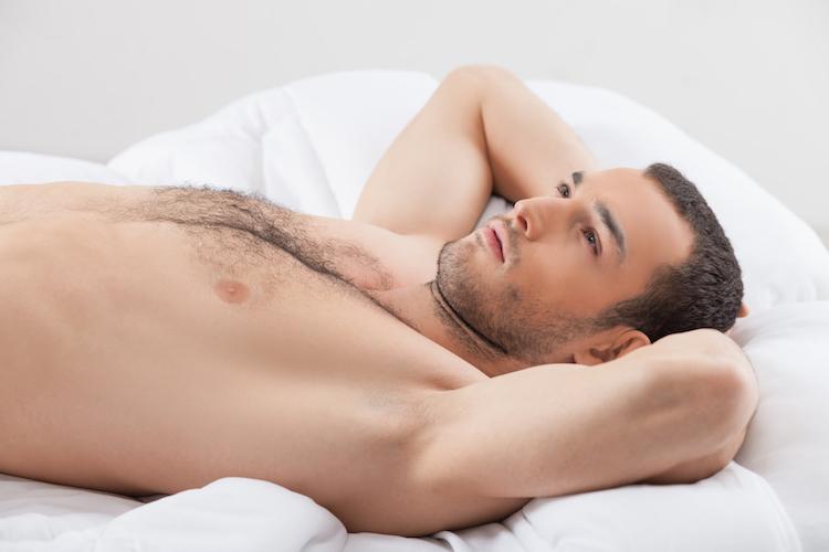 Attractive fit guy is relaxing in bedroom